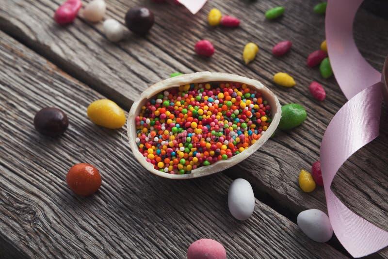L'uovo di cioccolato di Pasqua con la caramella variopinta spruzza immagine stock libera da diritti