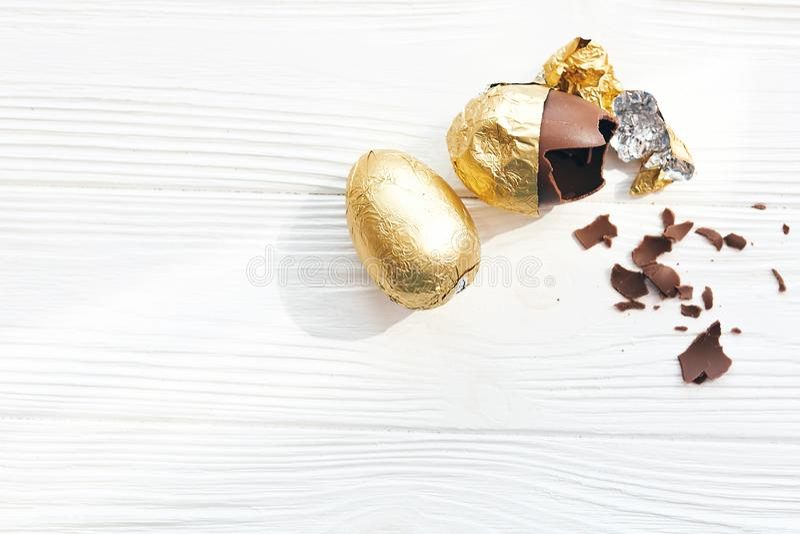 L'uovo di Pasqua alla moda in stagnola dorata e l'uovo di cioccolato rotto con i pezzi del cioccolato su fondo di legno bianco, p fotografia stock libera da diritti