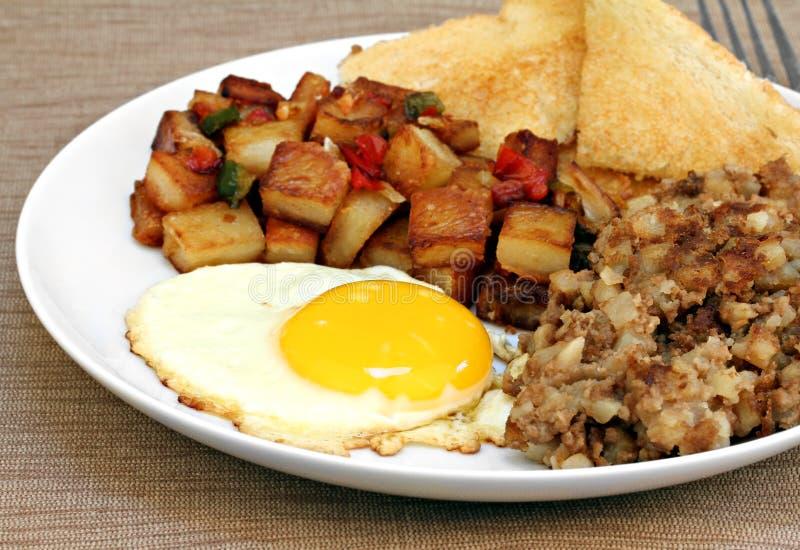 L'uovo fritto, le fritture della casa ed il hash fanno colazione. immagini stock