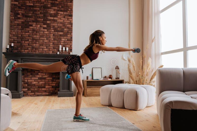 L'uso della sportiva mette ed esercitazione superiore con i pesi delle mani immagini stock