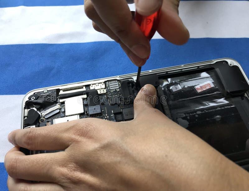 L'utente del computer portatile del libro di Apple Mac sta cambiando la batteria sola fotografia stock