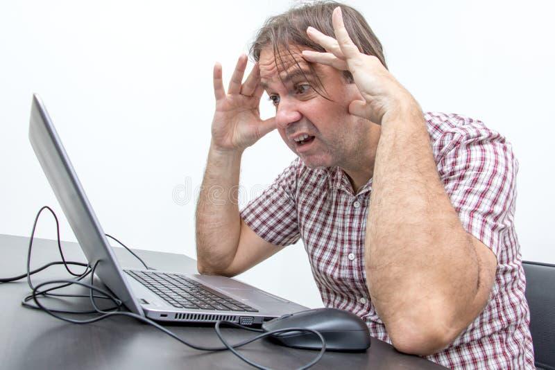 L'utente infelice confuso sta esaminando il computer immagine stock