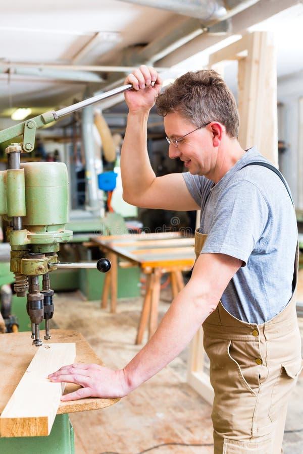 L'utilisation de charpentier électrique forent dedans la menuiserie photographie stock libre de droits