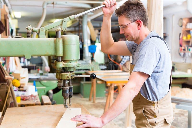 L'utilisation de charpentier électrique forent dedans la menuiserie photos stock