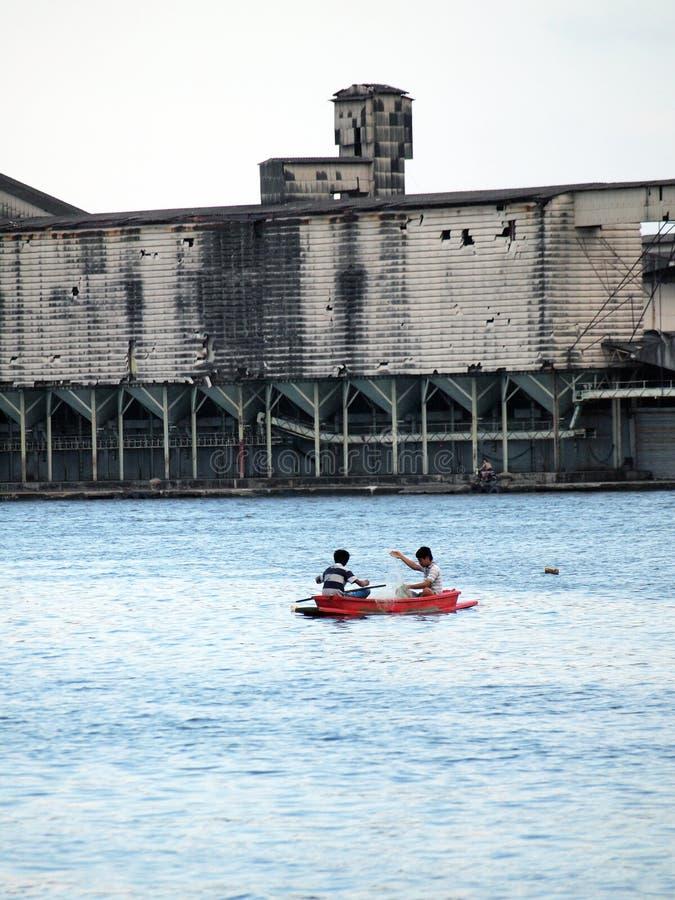 L'utilisation de pêcheur le le bateau et le filet traditionnels allant pêcher les poissons image libre de droits