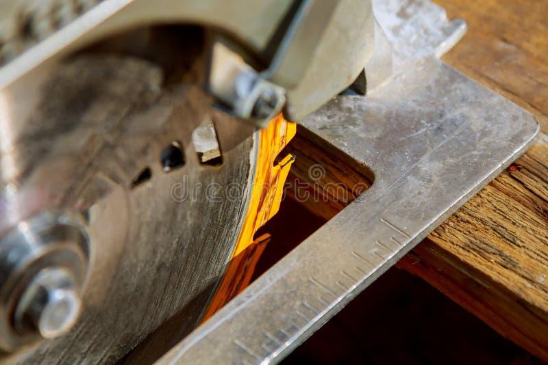 L'utilisation de travailleur de la construction a vu ou la circulaire a vu pour couper le bois image stock