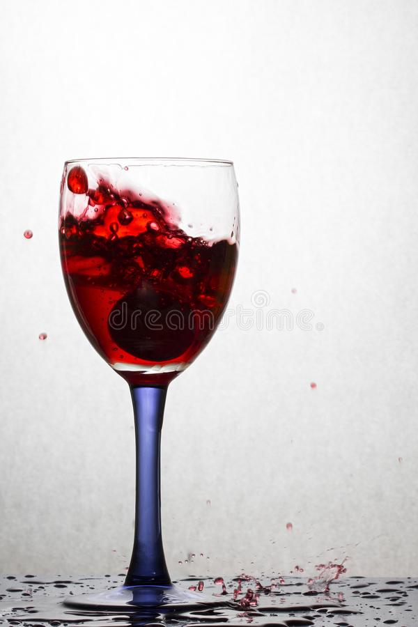 L'uva caduta in un vetro di vino rosso ha formato una bella spruzzata fotografia stock libera da diritti