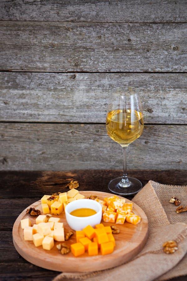 L'uva, il formaggio, i fichi ed il miele con un vetro di vino bianco sopra corteggiano fotografia stock