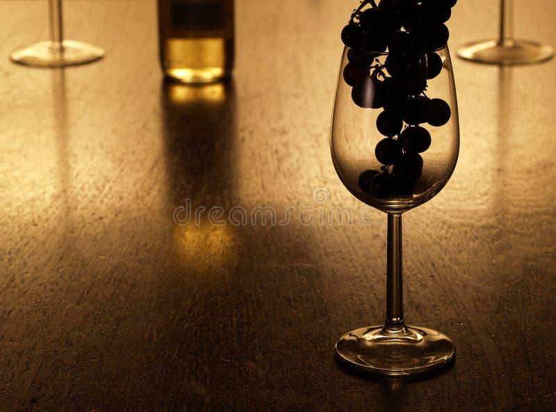 L'uva proietta in un bicchiere di vino immagine stock libera da diritti