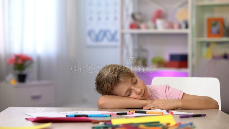?l?ve du cours pr?paratoire masculin dormant sur le bureau, les crayons de couleur et le papier sur la table de jardin d'enfants photographie stock