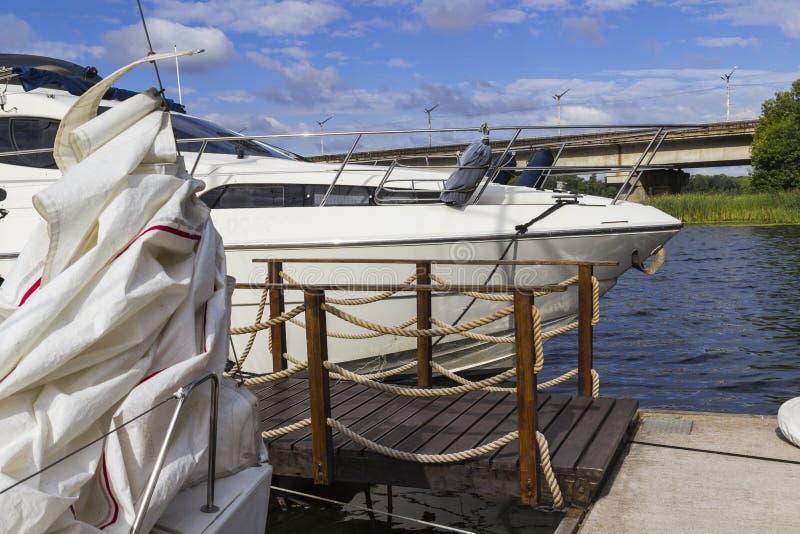 L'yacht è attraccato al pilastro del fiume, vicino ad un brid di legno fotografia stock libera da diritti