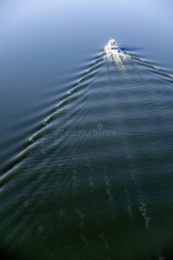 L'yacht con le piattaforme e le cabine taglia da parte a parte la superficie scura dell'acqua che lascia le onde e la traccia bia fotografia stock libera da diritti