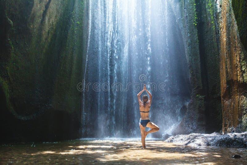 L'yoga, bella donna pratica nell'armonia della cascata, del corpo e di mente fotografie stock