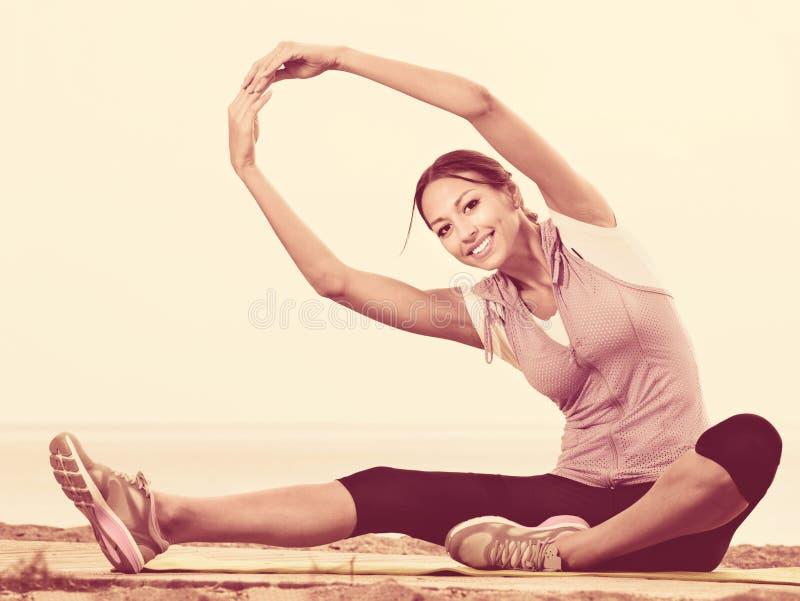 L'yoga di pratica della donna posa la seduta sulla spiaggia dal mare fotografia stock