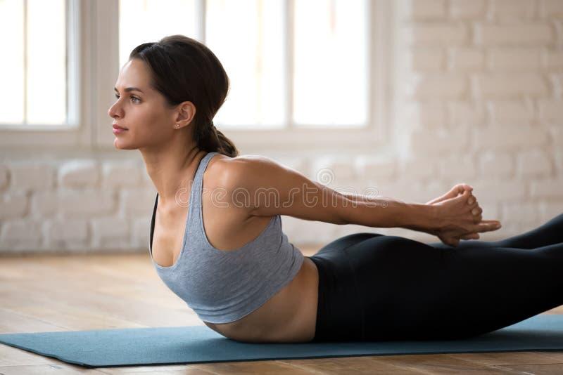 L'yoga di pratica della giovane donna, doppia gamba dà dei calci alla fine di esercizio su fotografia stock libera da diritti