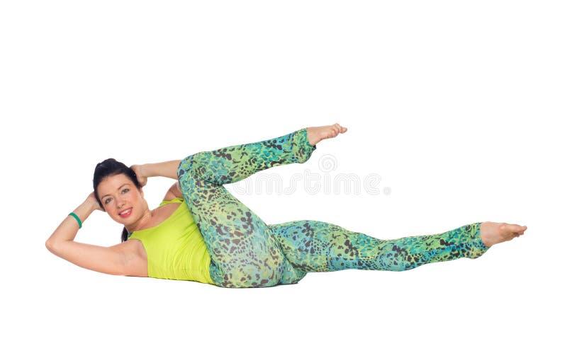 L'yoga di pratica della giovane donna, trovantesi sopra appoggia con i piedi sul variatio fotografie stock