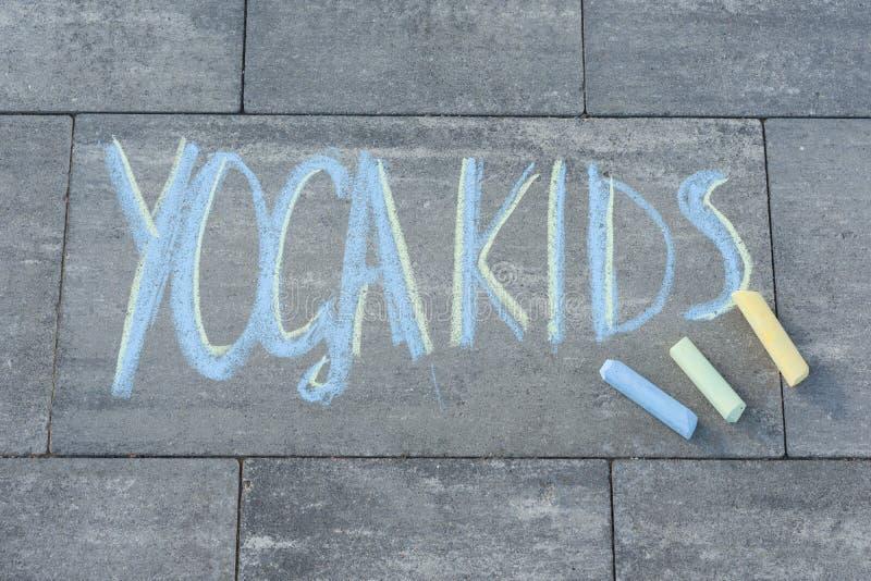 L'yoga scherza il testo scritto dai bambini sulla lastra per pavimentazione con i pastelli colorati fotografie stock libere da diritti