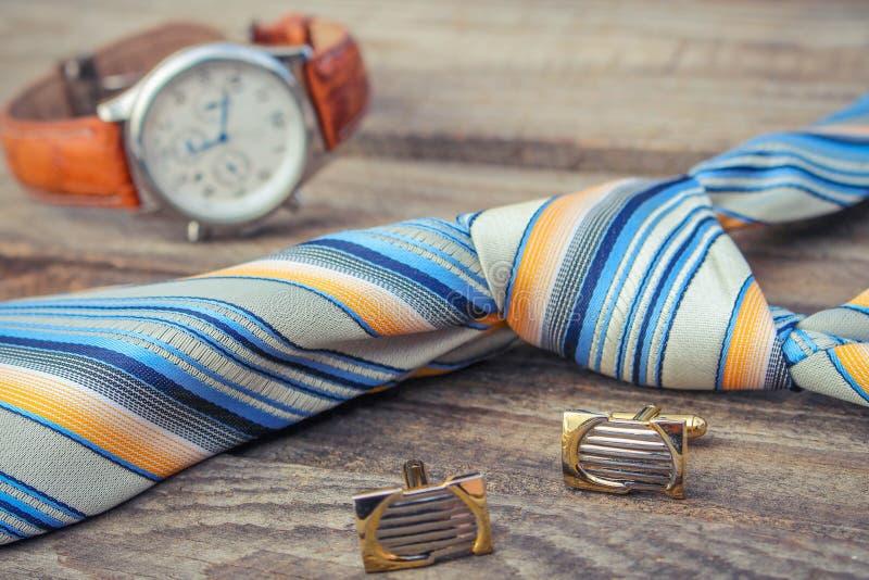 Laço, botão de punho e relógios no fundo de madeira velho imagem de stock royalty free
