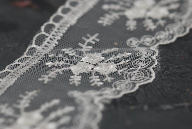 Laço branco beira bordada na superfície da obscuridade Fundo da textura do laço em Gray Board escuro fotos de stock