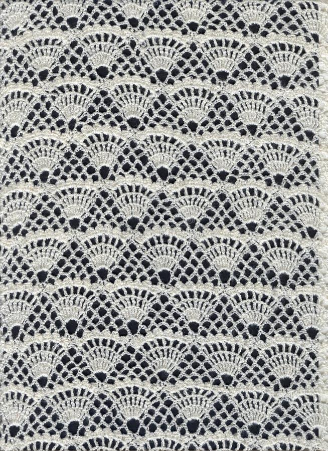 Laço branco em um fundo preto Laço feito malha em um fundo preto abstraia o fundo Textura fotografia de stock royalty free