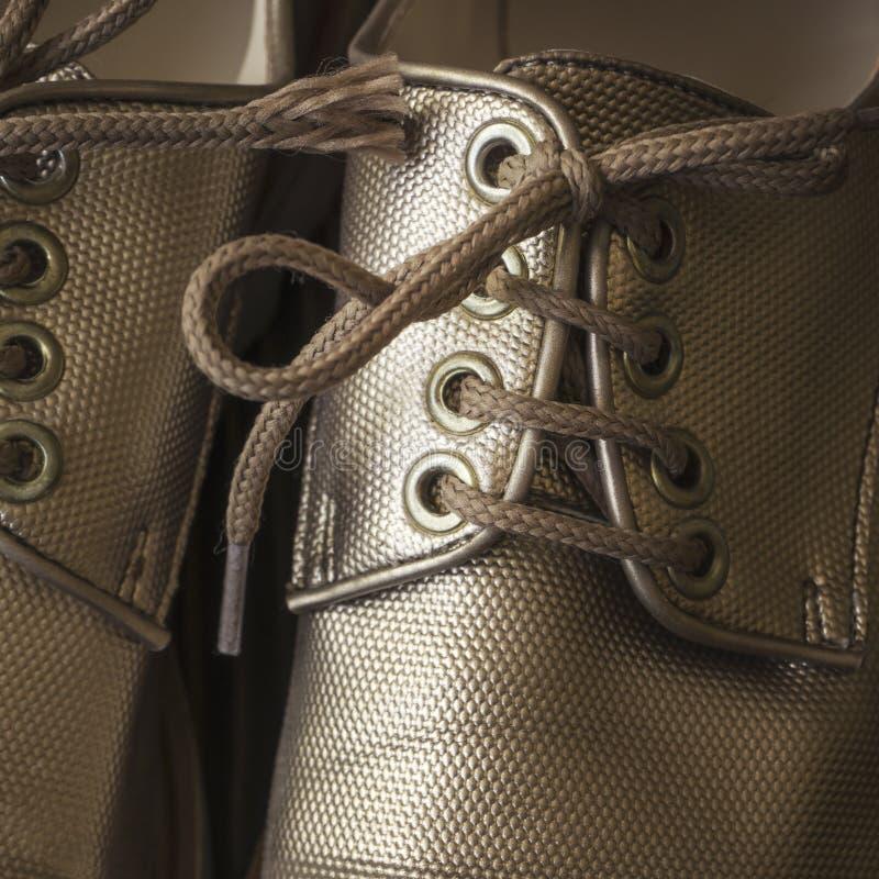 Laço em sapatas ascendentes e marrons do fim fotografia de stock