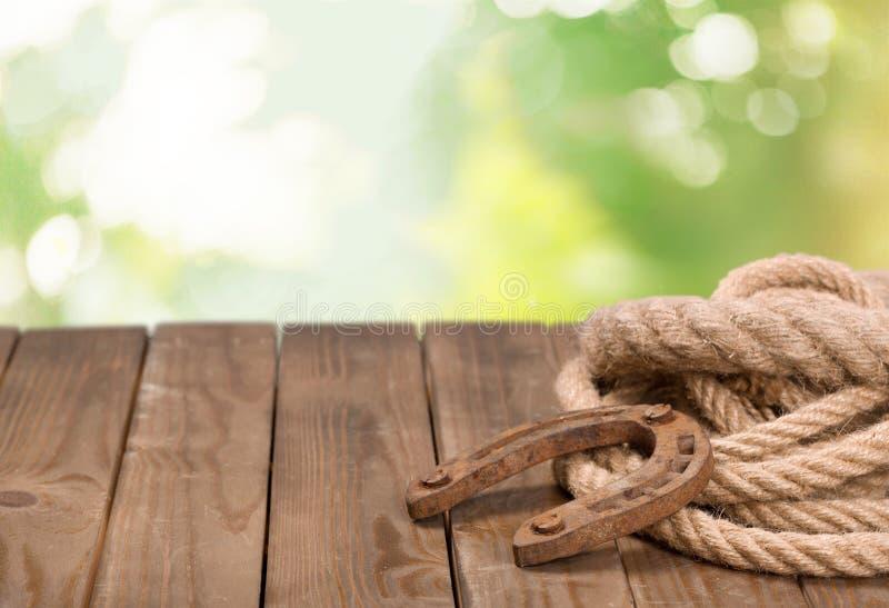 Laço velho da ferradura e do vaqueiro na tabela de madeira imagem de stock