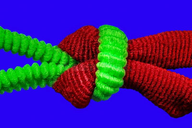 Laço vermelho e verde do cabelo em um macro do nó em um fundo azul imagem de stock royalty free