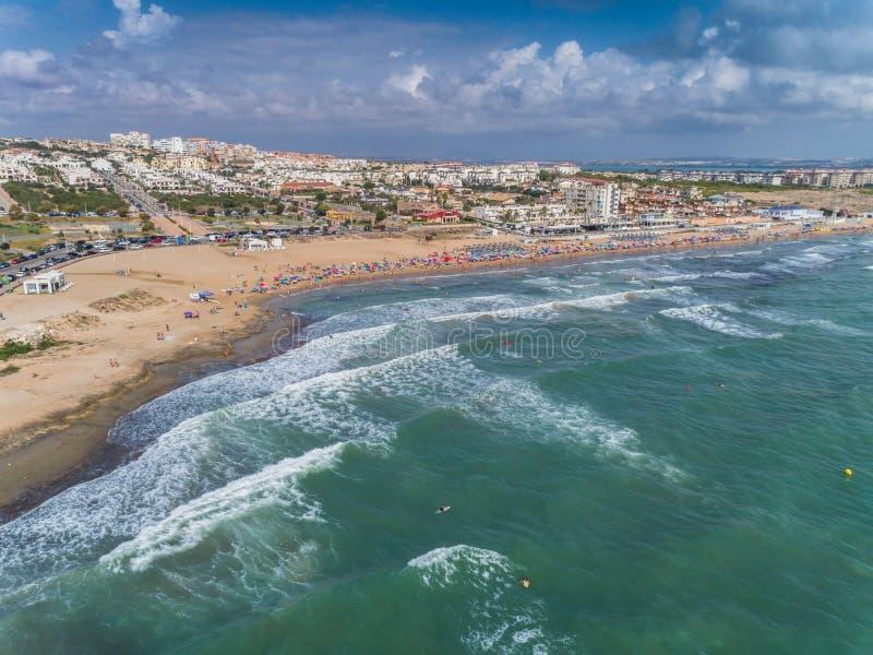 La末多海滩空中全景照片  冲浪者乘波浪 阿利坎特省肋前缘布朗卡 在西班牙2南部 免版税库存照片