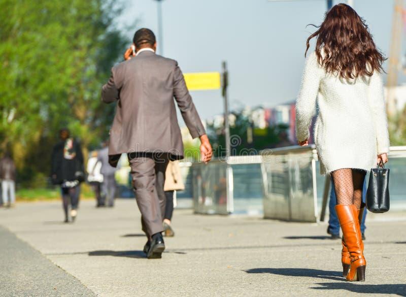 La防御,法国2014年4月10日:走与在街道上的袋子的女商人的画象 她佩带短裙和典雅的增殖比 免版税图库摄影