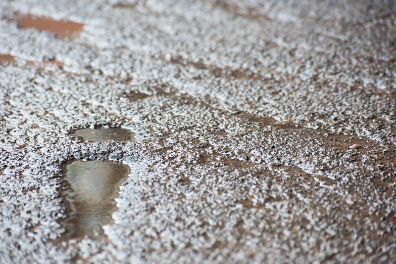 La abolladura bajo la forma de rastro de los zapatos en el asfalto llenó de agua imagen de archivo
