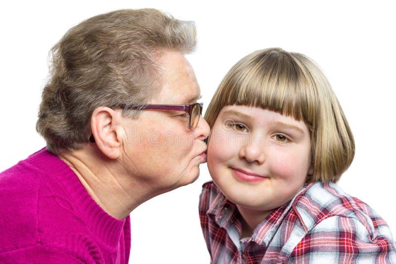 La abuela besa al nieto en mejilla imagenes de archivo