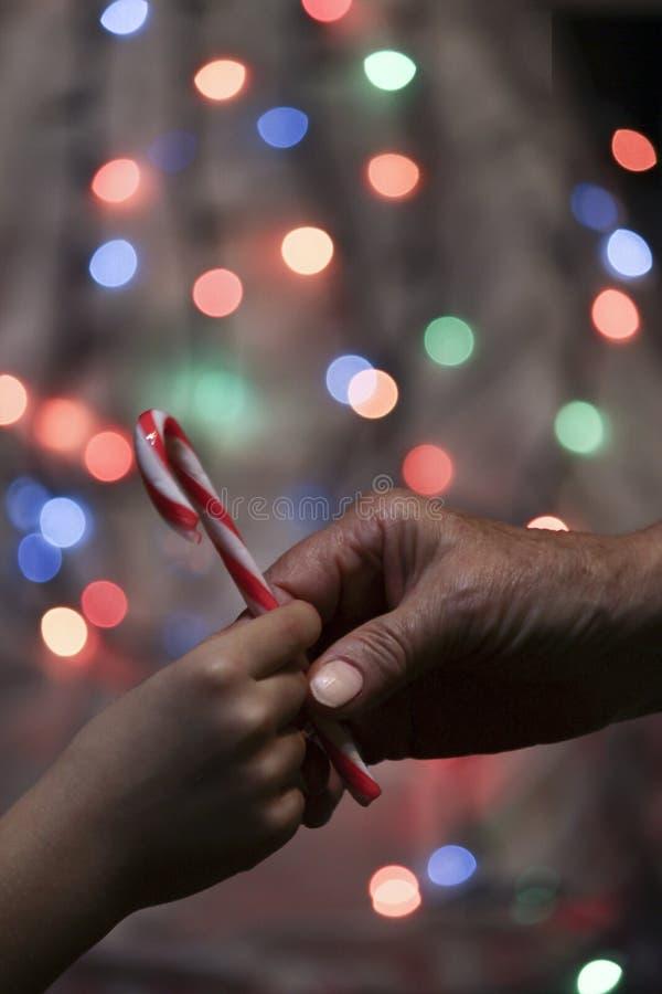 La abuela da el caramelo a un niño imagen de archivo libre de regalías