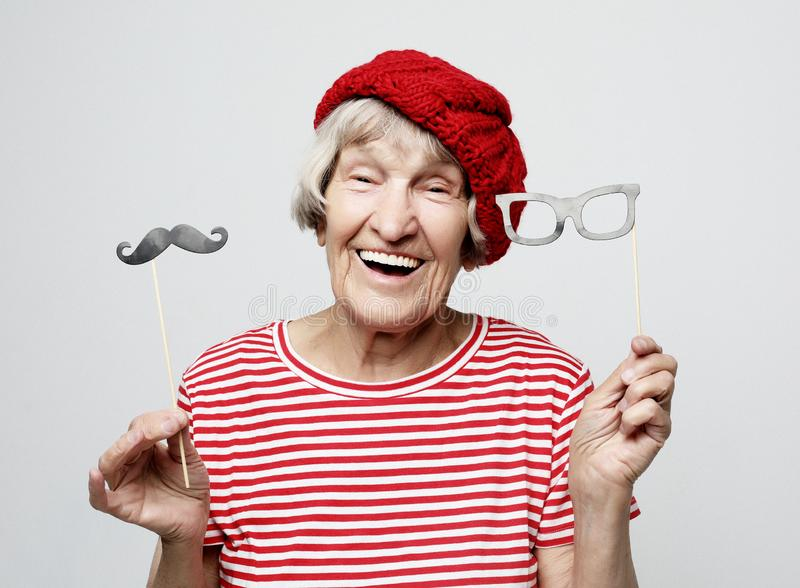 La abuela divertida con el bigote y los vidrios falsos, ríe y se prepara para el partido sobre fondo gris fotos de archivo