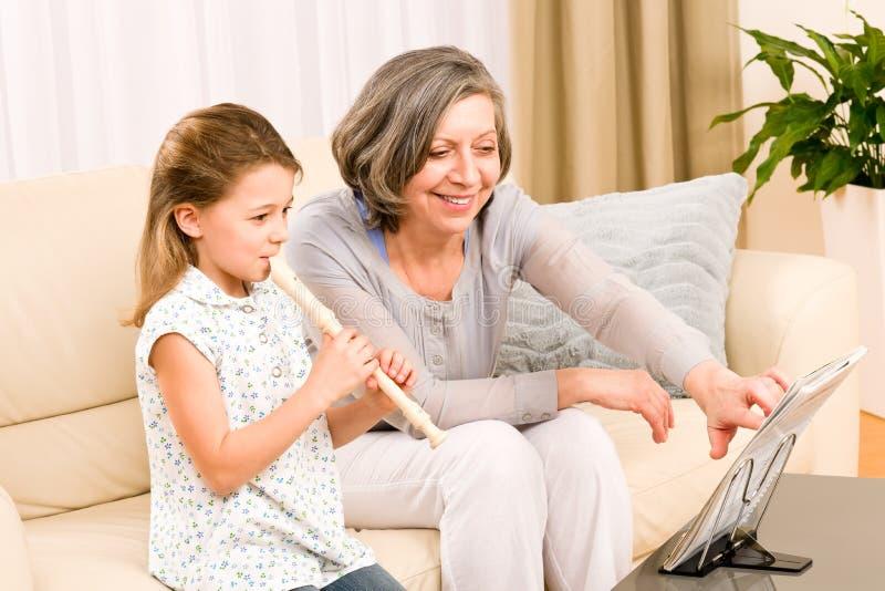 La abuela enseña a la flauta del juego de la chica joven feliz fotos de archivo