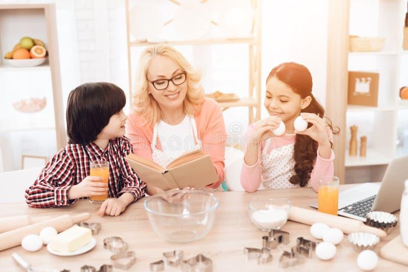La abuela hermosa en delantal, junto con sus nietos, mira el libro de cocina en cocina fotos de archivo libres de regalías