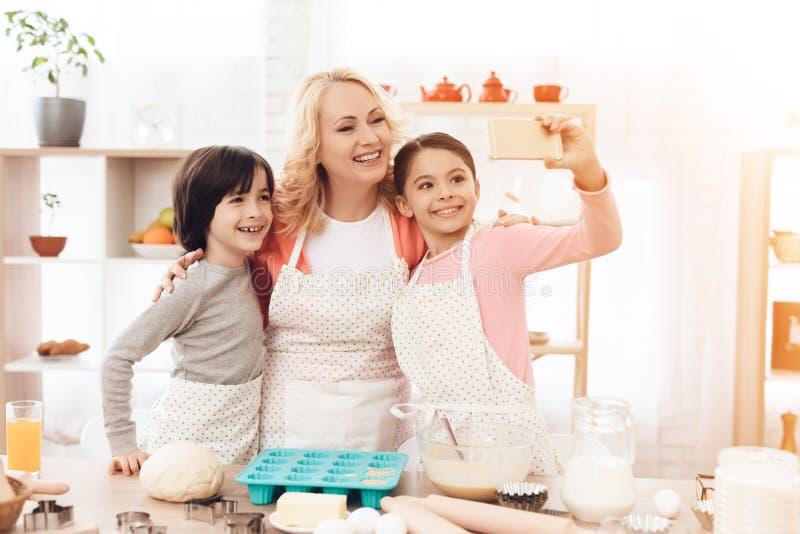 La abuela hermosa joven, junto con sus nietos, hace el teléfono del selfie en cocina foto de archivo libre de regalías