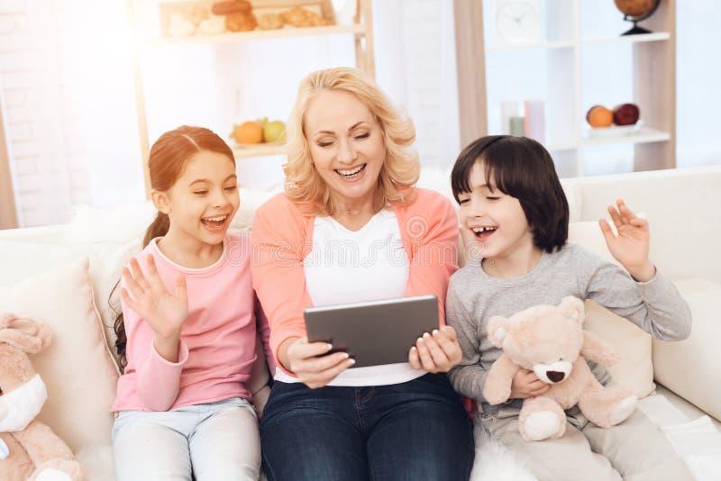 La abuela joven alegre con los nietos en humor envía saludos alguien en la tableta foto de archivo