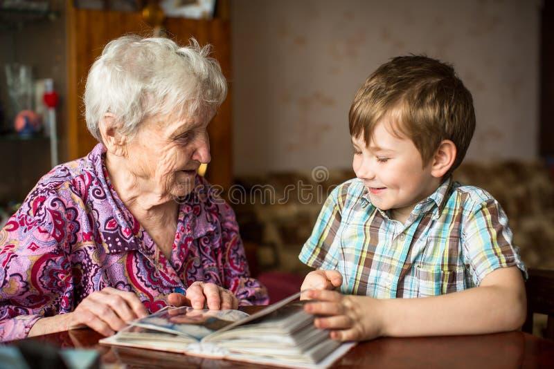 La abuela muestra el álbum de foto al pequeño nieto Amor imagen de archivo libre de regalías