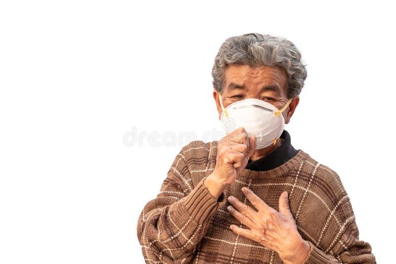 La abuela utiliza una máscara para prevenir el polvo aislado en el fondo blanco imagenes de archivo