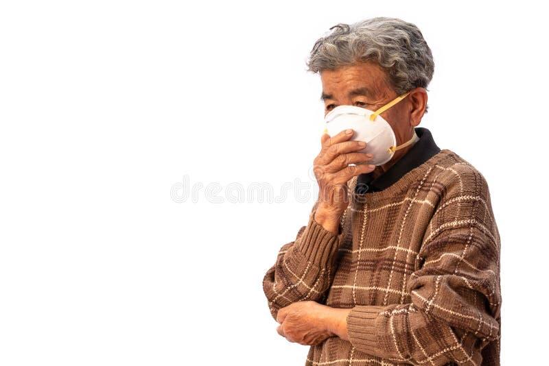 La abuela utiliza una máscara para prevenir el polvo aislado en el fondo blanco imagen de archivo libre de regalías