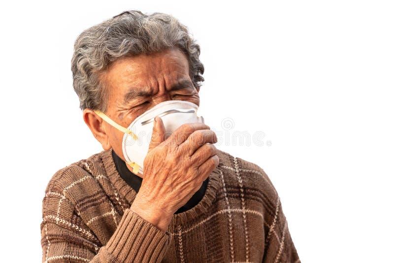 La abuela utiliza una máscara para prevenir el polvo aislado en el fondo blanco foto de archivo