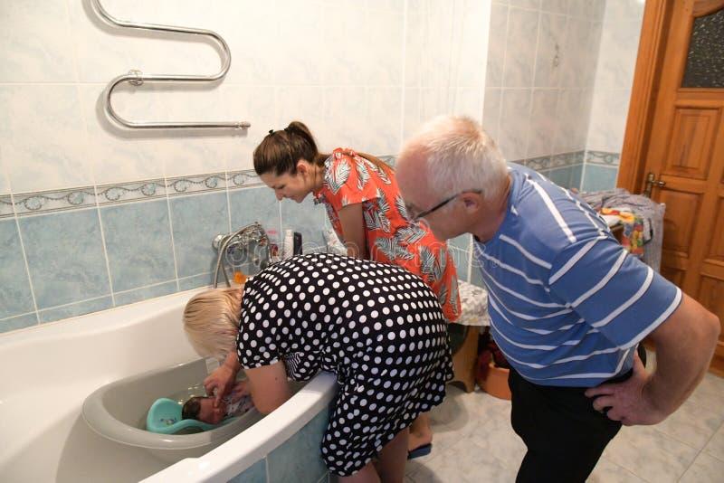La abuela y el abuelo bañan al niño, su nieto Familia feliz: abuelos con su nieto primero bañándose en casa foto de archivo libre de regalías
