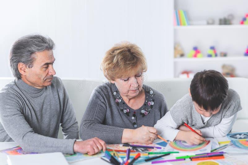 La abuela y el abuelo están dibujando un arco iris con su nieto imagen de archivo