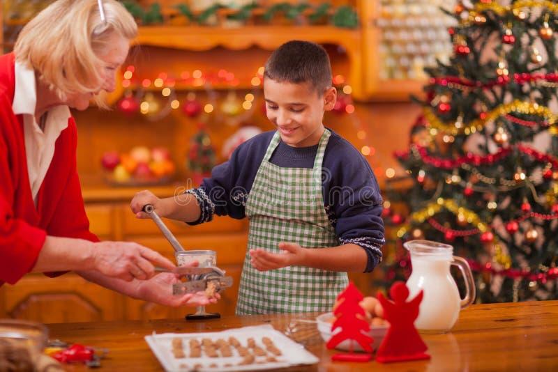 La abuela y los nietos del tiempo de la familia que hacen la Navidad cocinan imagenes de archivo