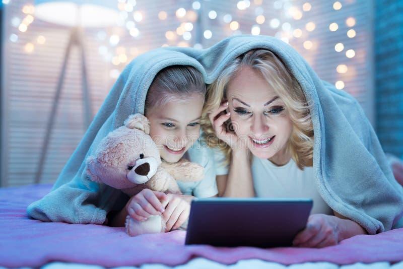 La abuela y la nieta están mirando película en la tableta debajo de la manta en la noche en casa fotos de archivo libres de regalías