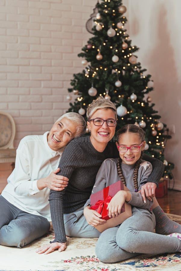La abuela y la nieta que adornaban una Navidad treeFamily recolectaron alrededor de un árbol de navidad, generaciones femeninas imágenes de archivo libres de regalías