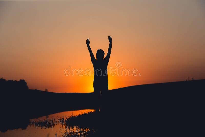 La acción de gracias de la muchacha agradece a dios en la puesta del sol fotos de archivo