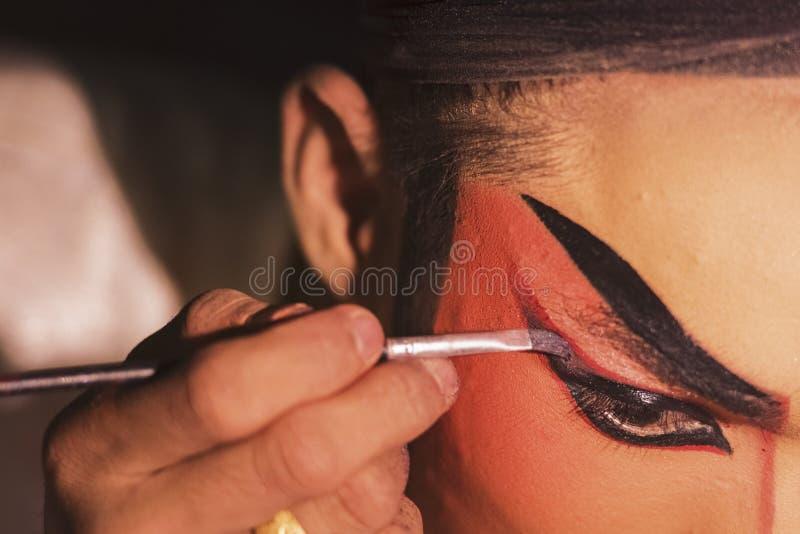 La actriz china de la ópera está pintando su cara entre bastidores imágenes de archivo libres de regalías