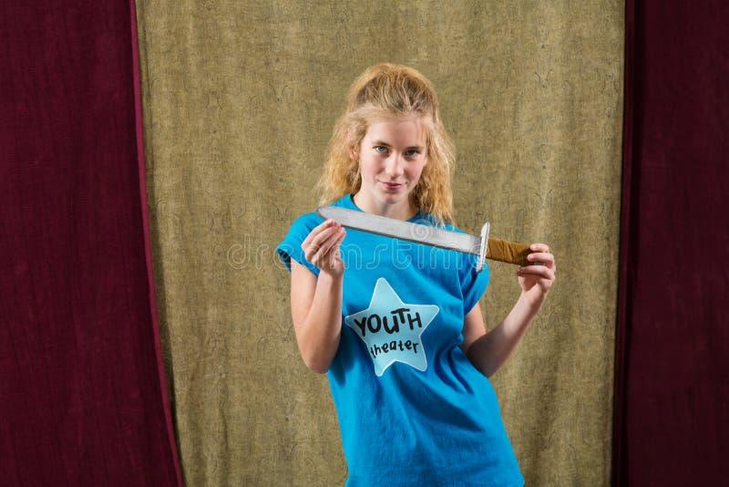 La actriz de sexo femenino joven sostiene la daga foto de archivo
