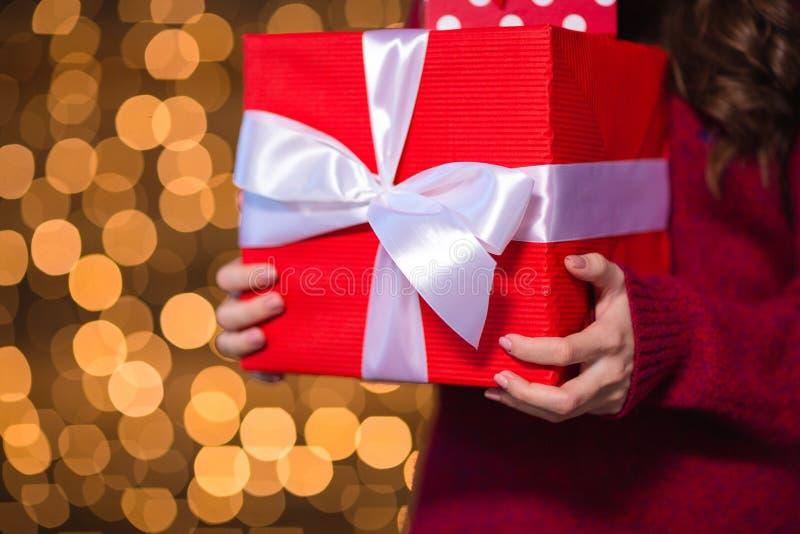 La actual caja del rojo holded por la hembra joven en suéter hecho punto imagen de archivo